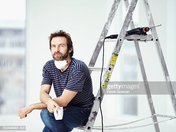 Mid adult man sitting on ladder in room, holding mug, portrait