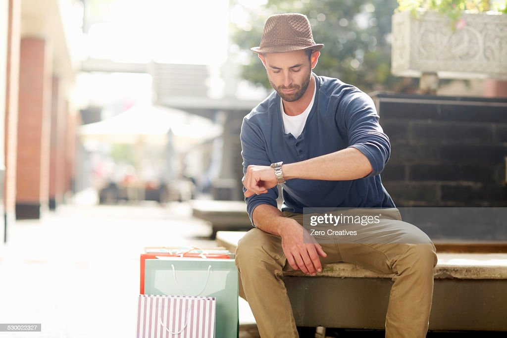 Mid adult man sitting on seat, looking at watch, shopping bags beside him