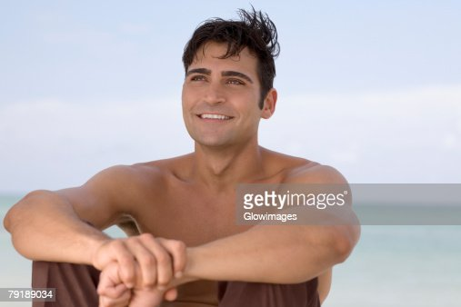 Mid adult man sitting on the beach and smiling : Foto de stock