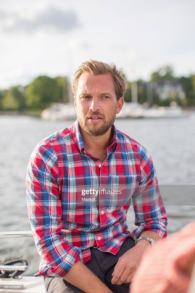 Mid adult man sitting on yacht at river