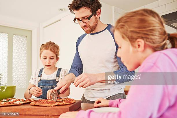 Mid adult man slicing pizza for daughters at kitchen bench