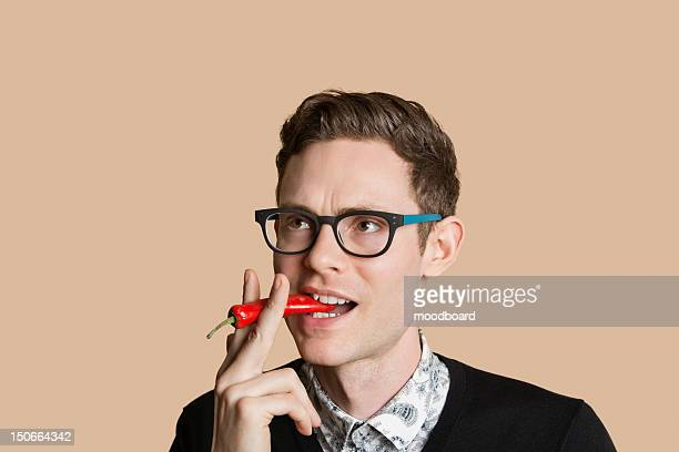 Mid adult man smoking red chili pepper over colored background