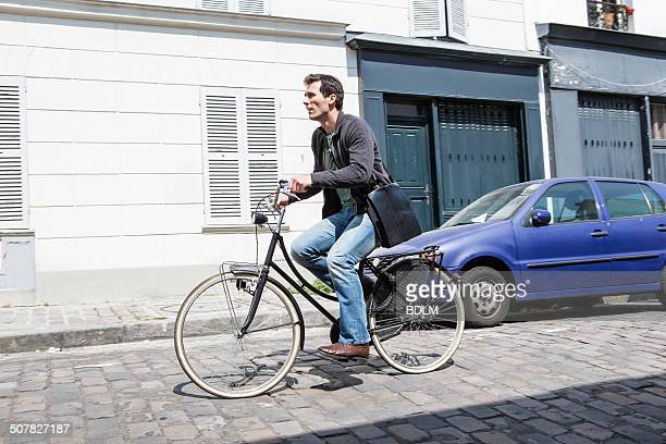 Mid adult man speeding down cobbled city street on bicycle