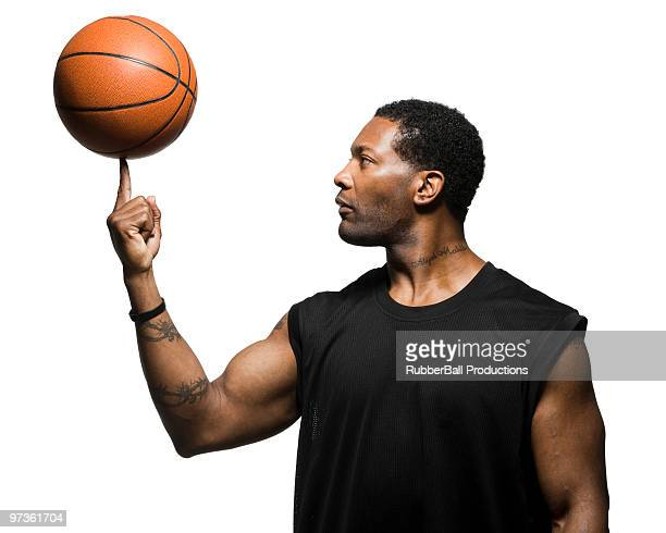 Mid adult man spinning basketball in air