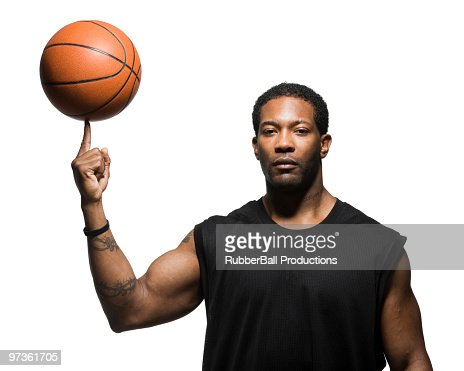 Mid adult man spinning basketball in air, portrait