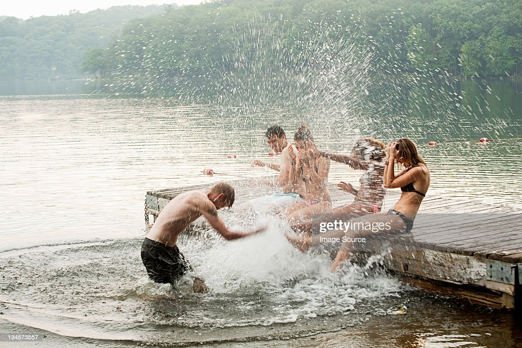 Mid adult man splashing friends in lake : Stock Photo