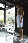 A Mid Adult Man Standing at the Outdoor Hot Spring Bath, Low Angle View, Side View, Full Length