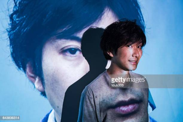 Mid adult man standing in a projected image of himeself
