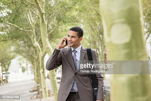 Mid adult man standing on pavement and talking on cell phone : Stock Photo