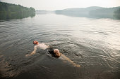 Mid adult man swimming in lake