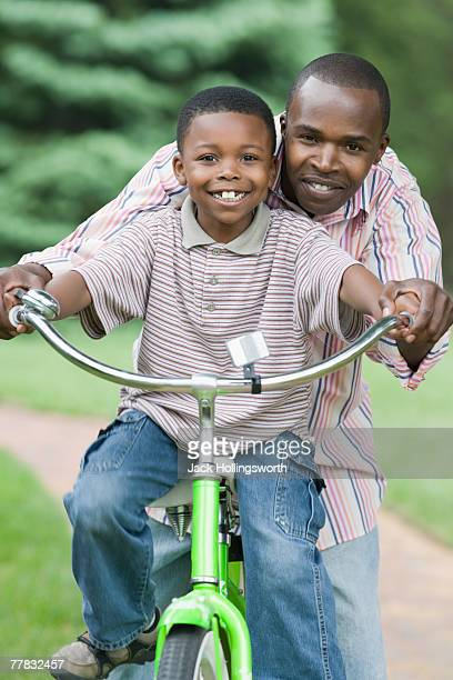 Mid adult man teaching his son how to ride a bicycle