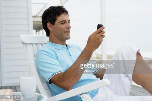 Mid adult man text messaging near beach