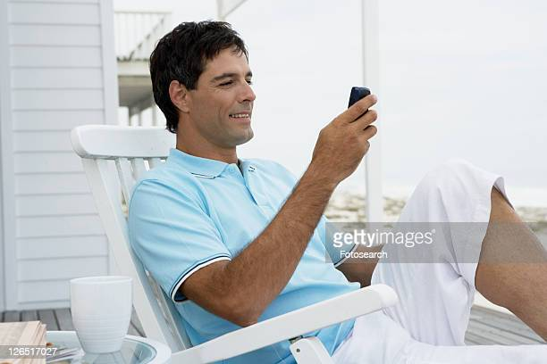 Mid adult man text messaging near beach