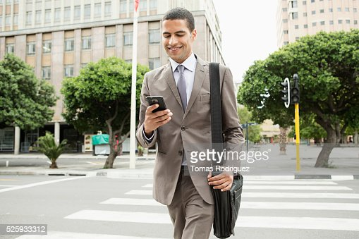 Mid adult man text messaging while crossing street : Foto stock