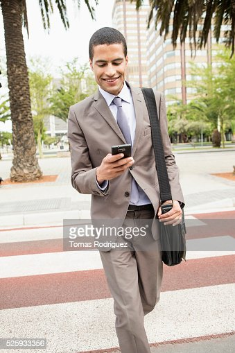 Mid adult man text messaging while crossing street : Stock-Foto