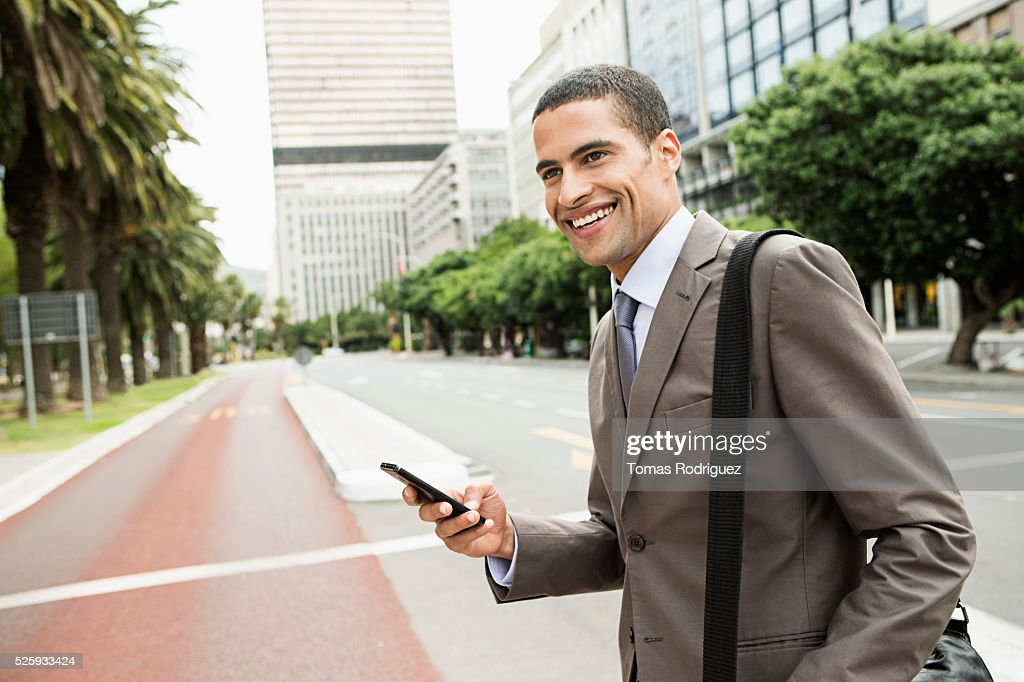 Mid adult man text messaging while crossing street : Stock Photo