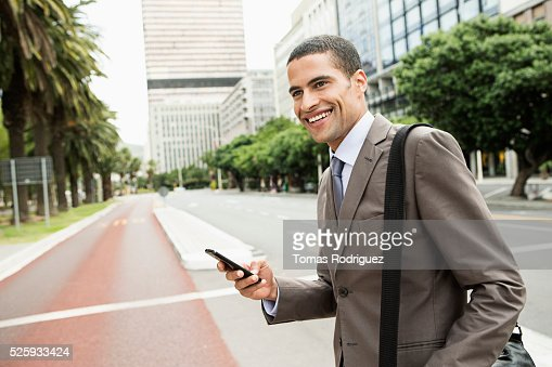 Mid adult man text messaging while crossing street : Photo
