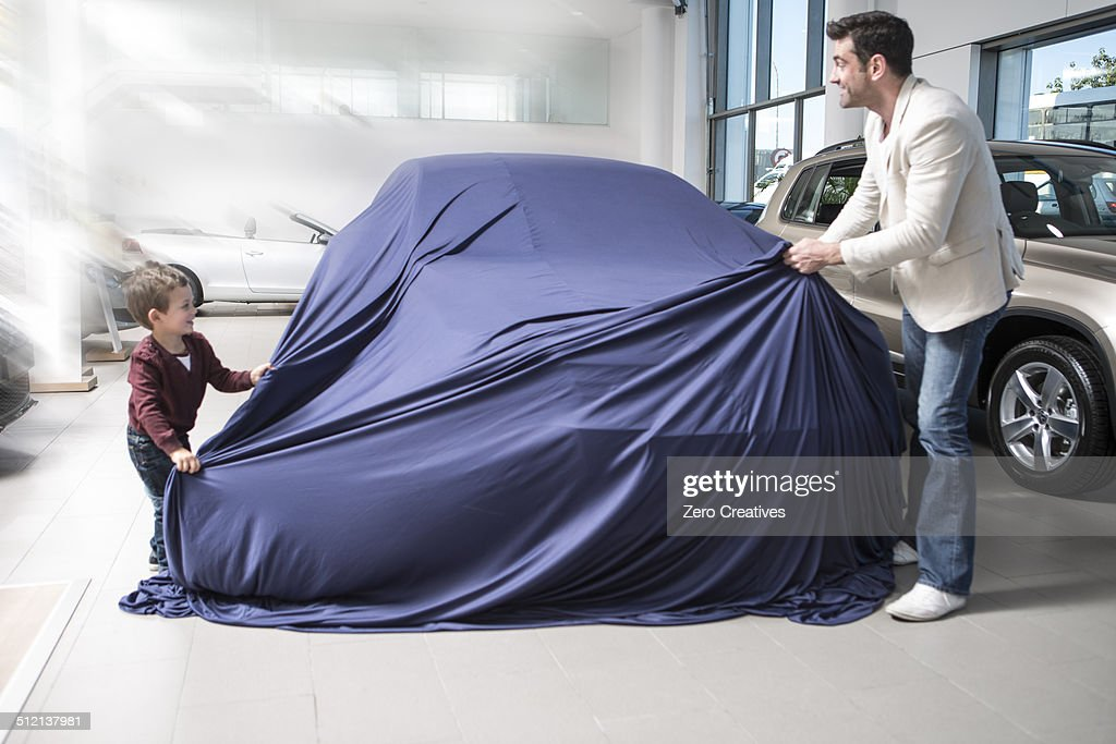 Mid adult man uncovering new car with son in car dealership