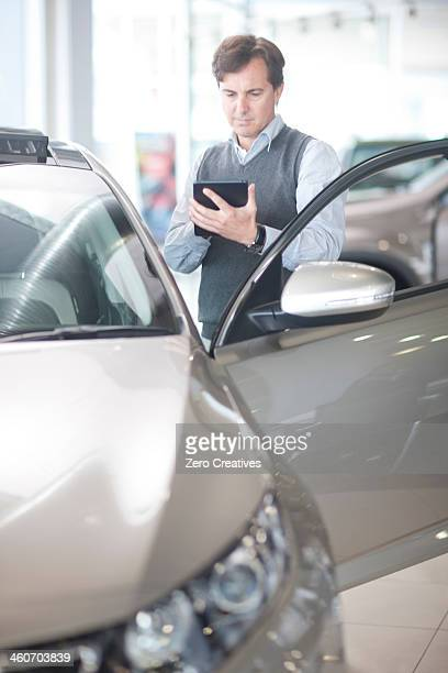 Mid adult man using calculator in car showroom