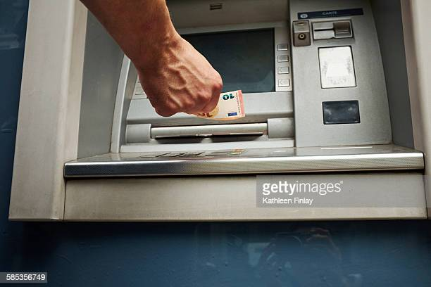 Mid adult man using cash machine, focus on hands