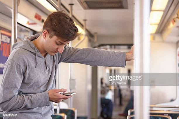 Mid adult man using cellphone on subway train