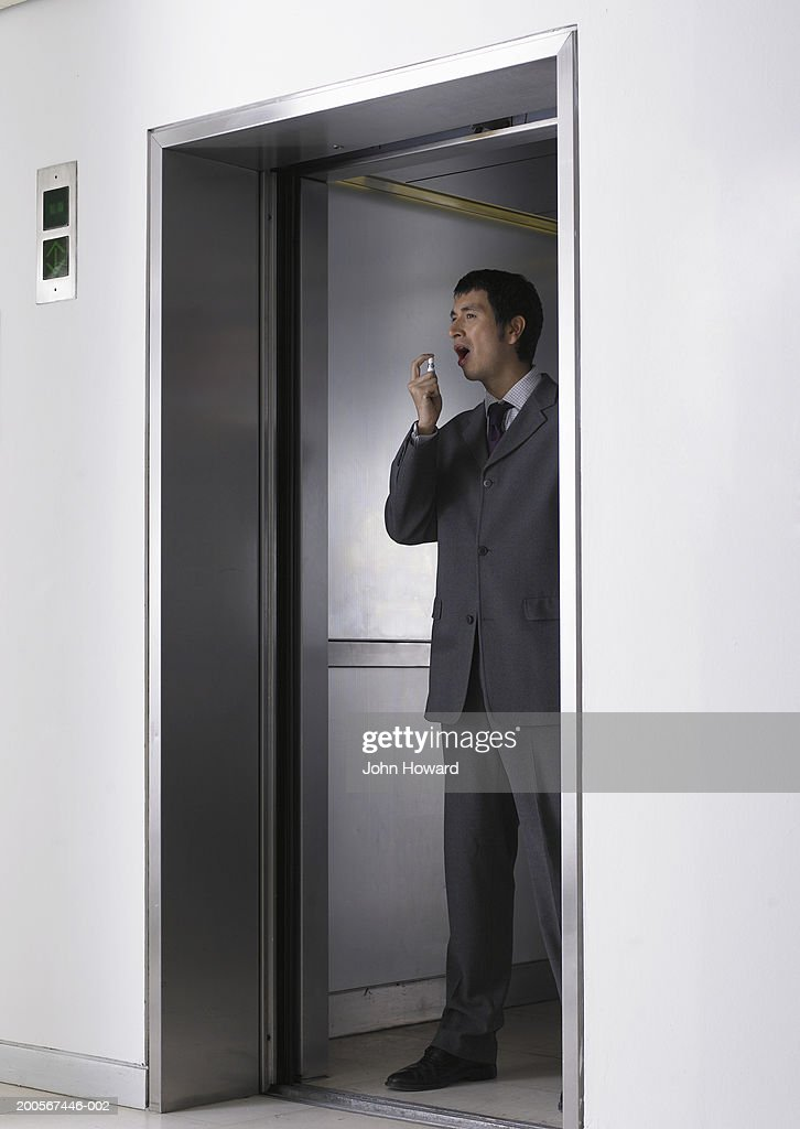 Mid adult man using inhaler in elevator : Stock Photo