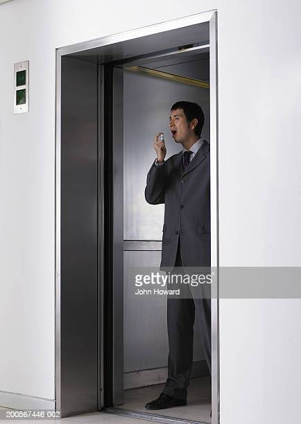 Mid adult man using inhaler in elevator