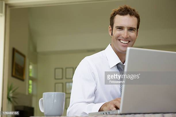 Mid adult man using laptop in living room (low angle view)
