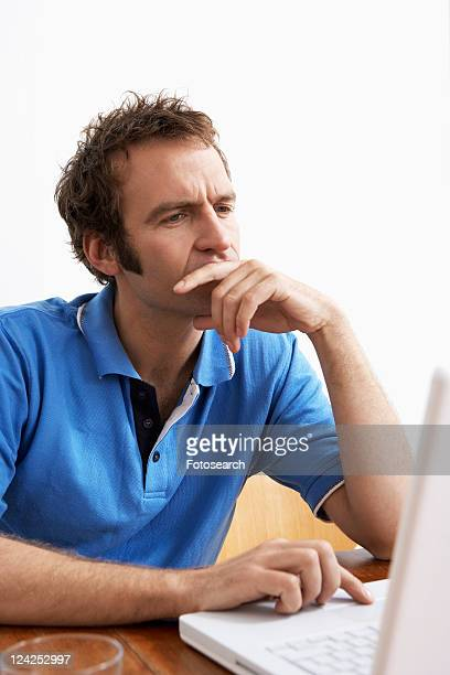 Mid adult man using laptop