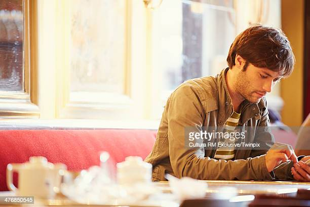 Mid adult man using mobile in cafe