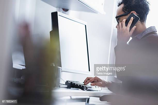 Mid adult man using phone and computer in office