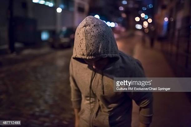 Mid adult man walking the street at night with hood up and head down