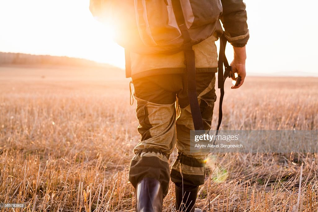 Mid adult man walking through fields, rear view, low section