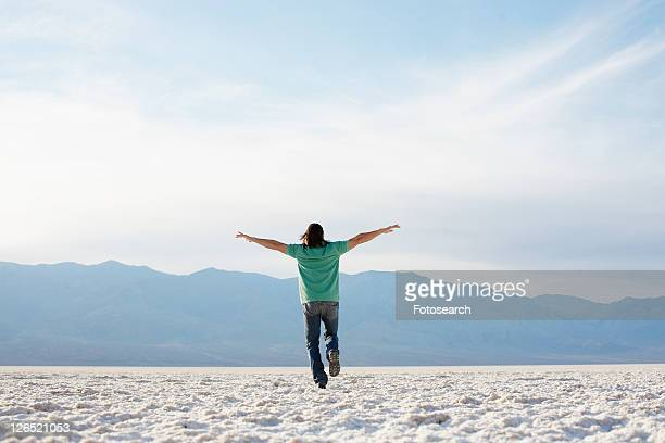 Mid adult man walking with arms outstretched in desert