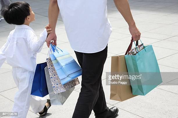 Mid adult man walking with his son and carrying shopping bags