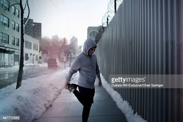 Mid adult man warming up for run on sidewalk