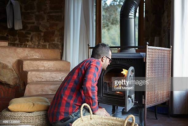 Mid adult man watching log burning fire