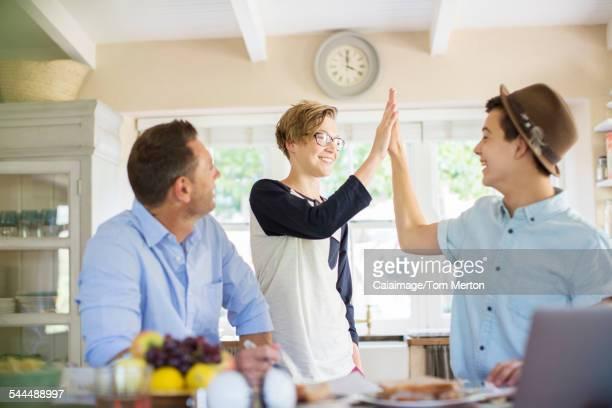 Mid adult man watching teenage boys doing high five