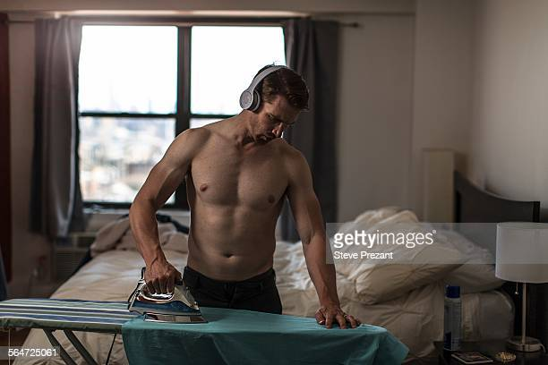 Mid adult man wearing boxer shorts listening to headphones whilst ironing