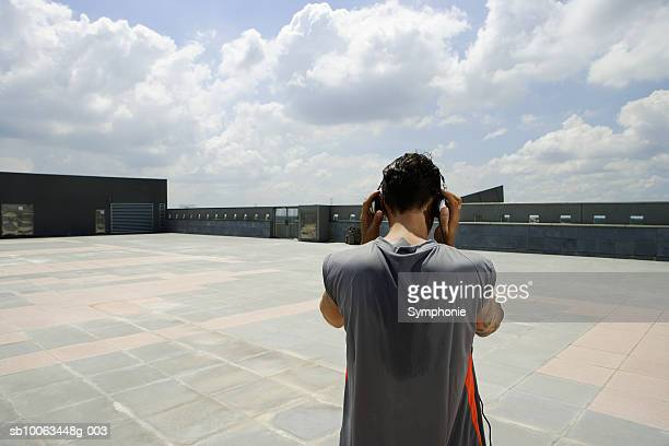 Mid adult man wearing headphones outdoors, rear view