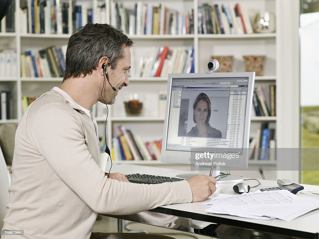 Mid Adult Man Wearing Headset Videoconferencing  with Woman : Stock Photo