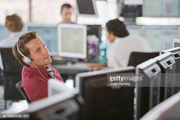 Mid adult man weraing headset in office, people in backgrpund