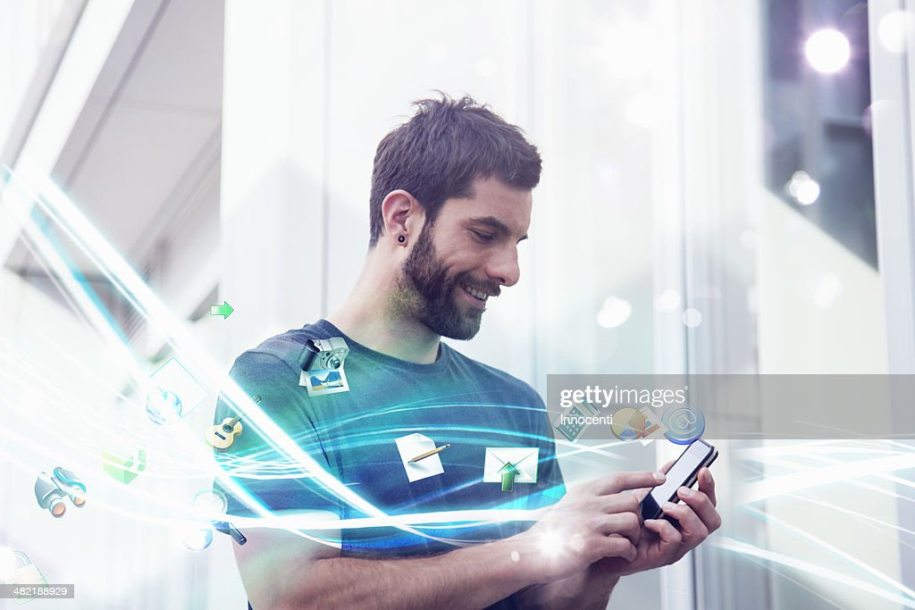 Mid adult man with apps and lights coming from smartphone : Stock Photo