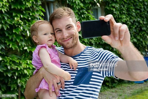 Mid adult man with baby daughter taking selfie on smartphone in garden