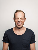 Mid adult man with expression feelings on his face studio shot series. in pain eyes closed.
