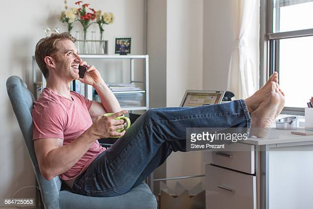Mid adult man with feet up on desk chatting on smartphone