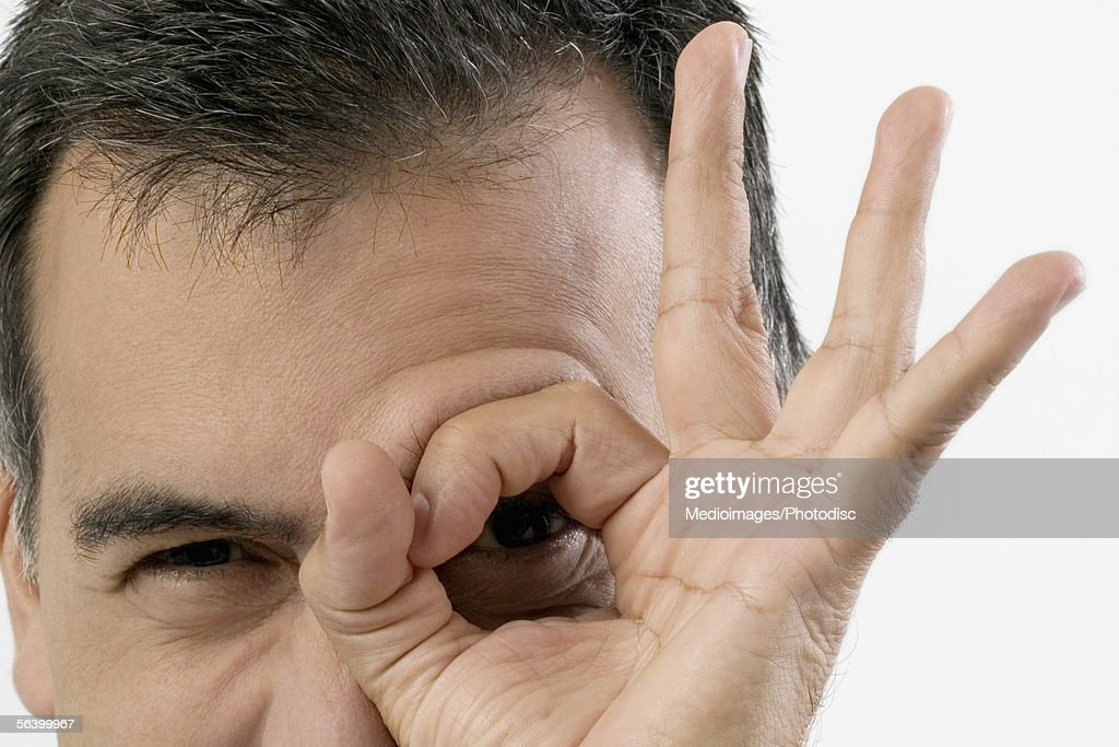 Mid Adult man with fingers in a circle in front of his eye : Stock Photo