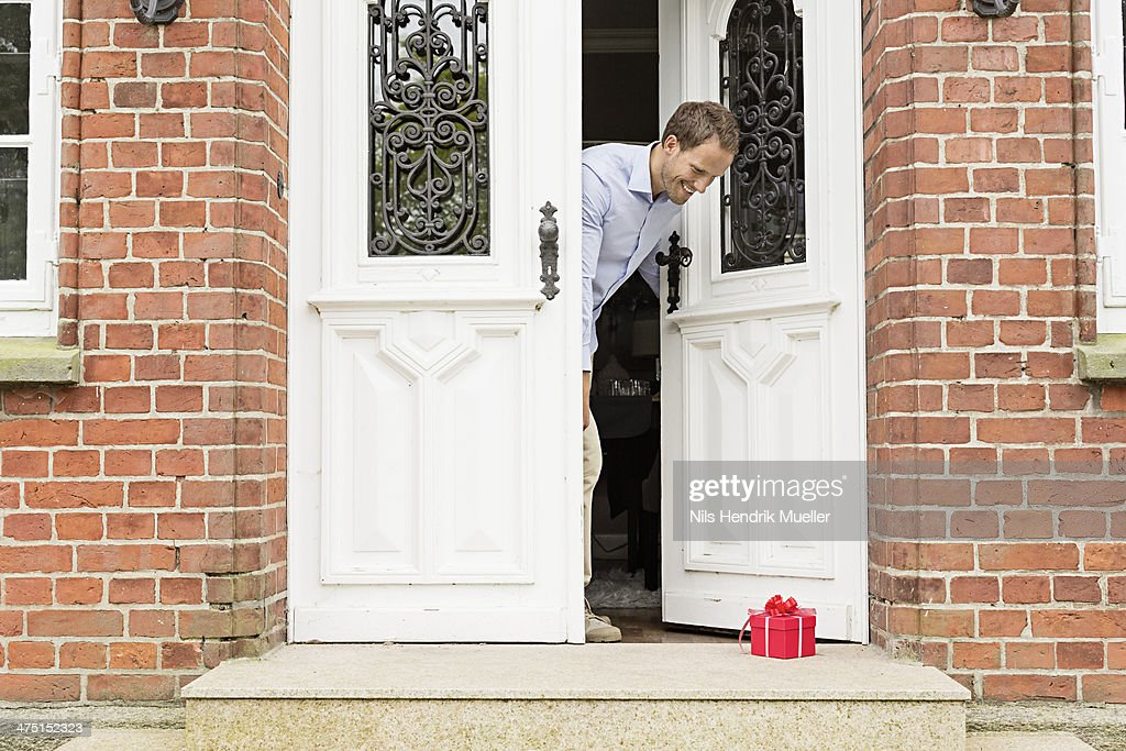 Mid adult man with gift on front doorstep