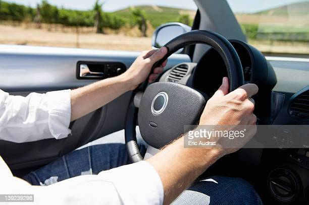 Mid adult man's hand holding a steering wheel of convertible car