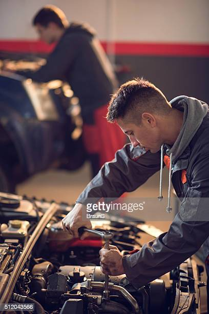 Mid adult mechanic repairing a car in auto repair shop.